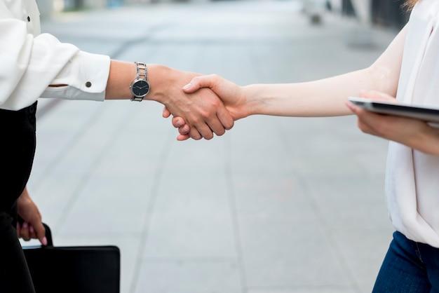 Femmes d'affaires tenant les mains dans la rue Photo gratuit