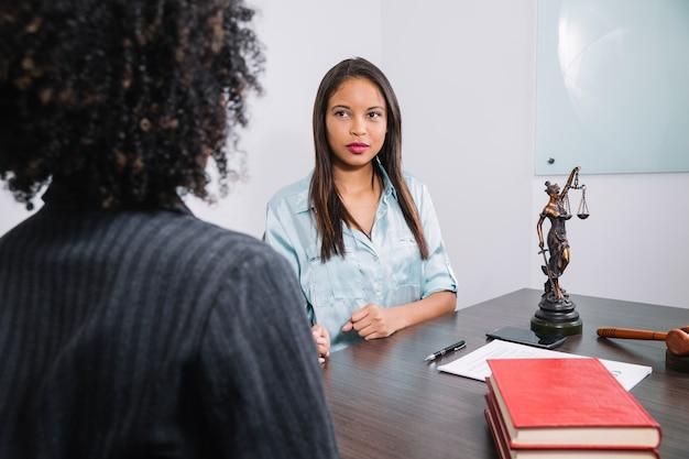 Femmes afro-américaines assis à table près de document, stylo, figure et marteau Photo gratuit