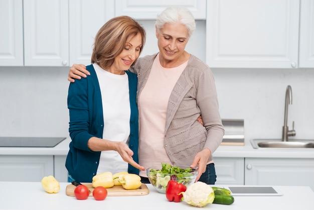 Femmes âgées avec des légumes sur la table Photo gratuit