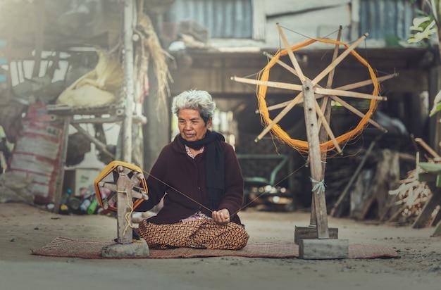 Des femmes âgées manifestent à la procédure de fabrication du tissage de la soie thaïlandaise Photo Premium