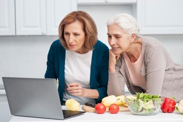 Femmes âgées à la recherche de recettes de cuisine Photo gratuit