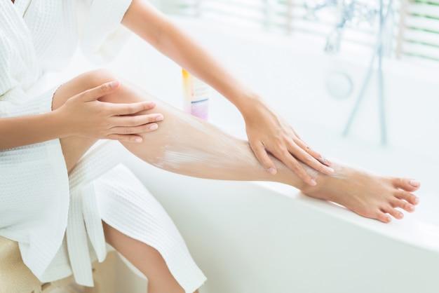 Les femmes appliquent une lotion sur les jambes. après le bain Photo Premium