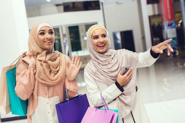 Femmes arabes avec des colis debout dans le centre commercial. Photo Premium