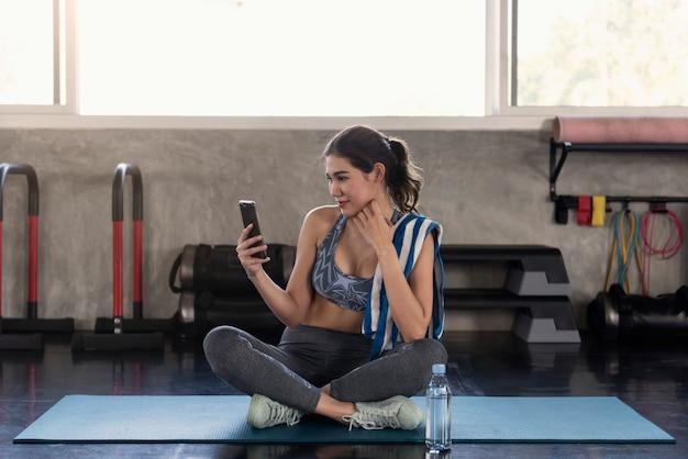 Femmes Asiatiques à L'aide De Smartphone Après L'exercice Dans La Salle De Fitness. Se Détendre Style De Vie. Photo Premium