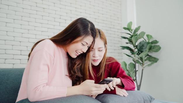 Femmes asiatiques à l'aide d'un smartphone vérifiant les médias sociaux dans le salon à la maison, groupe d'ami en colocation Photo gratuit