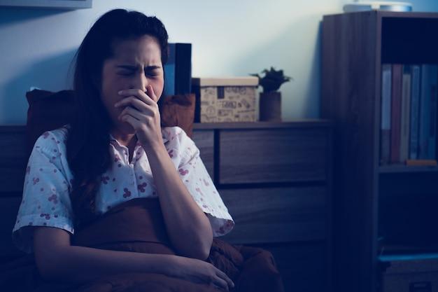 Les femmes asiatiques baillent pendant son réveil dans le lit Photo Premium
