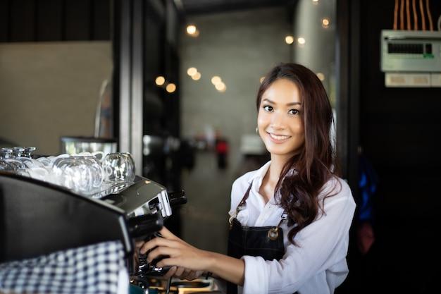 Femmes asiatiques barista souriante et utilisant une machine à café Photo Premium
