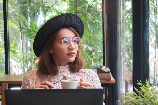 Femmes asiatiques avec café et travaillant sur ordinateur portable dans le café Photo Premium