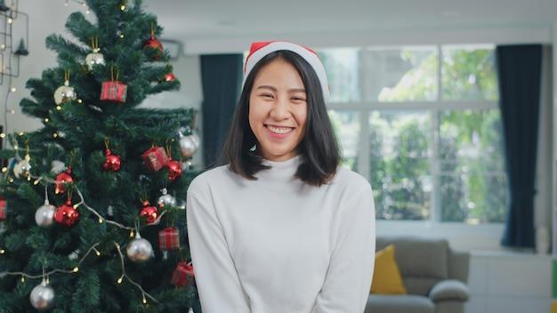 Les femmes asiatiques célèbrent la fête de noël. les femmes adolescentes portent un chapeau de noël relaxant souriant heureux à la recherche de vacances d'hiver de noël réunies dans le salon à la maison. Photo gratuit