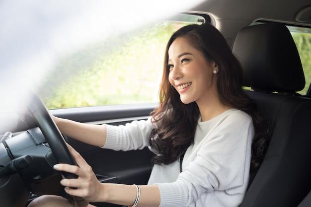 Les Femmes Asiatiques Conduisant Une Voiture Et Sourient Joyeusement Avec Une Expression Positive Heureuse Pendant Le Trajet En Voiture Photo Premium