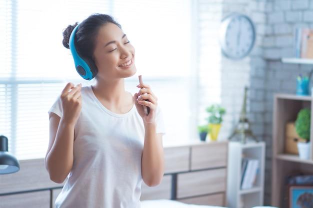 Les femmes asiatiques écoutent de la musique et chante joyeusement dans la chambre Photo Premium