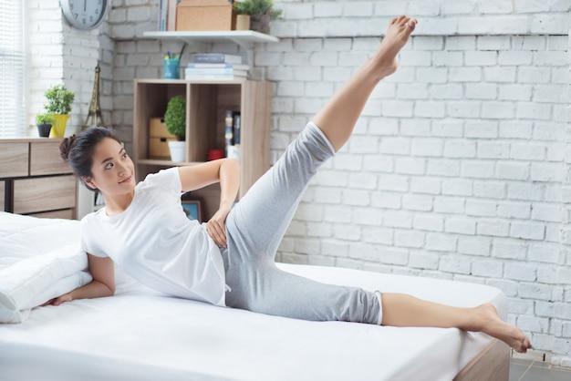 Les Femmes Asiatiques Exerçant Dans Le Lit Le Matin, Elle Se Sent Rafraîchi. Elle Agit Comme Un Squat. Photo Premium