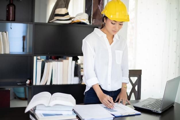 Femmes asiatiques ingénierie inspectant et travaillant et tenant des bleus au bureau Photo Premium