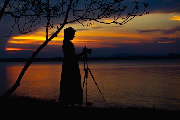 Femmes asiatiques photographiant se sentent bien sur la vue sur le lac et les montagnes avec un chapeau au moment des vacances Photo Premium