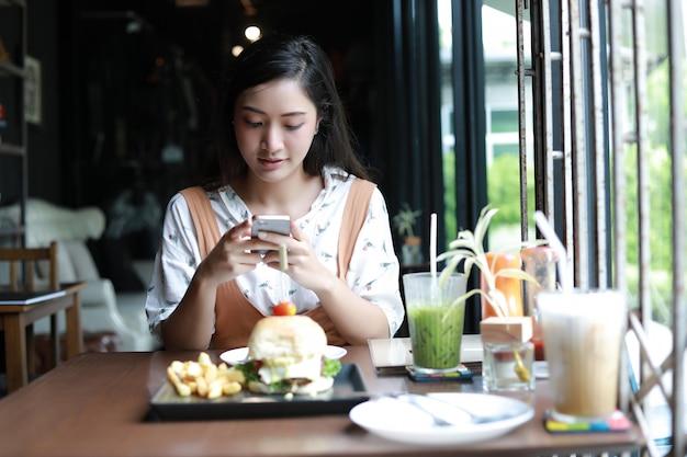 Femmes asiatiques prenant des photos de hamburgers et apprécié de manger au café et au restaurant sur le temps de se détendre Photo Premium