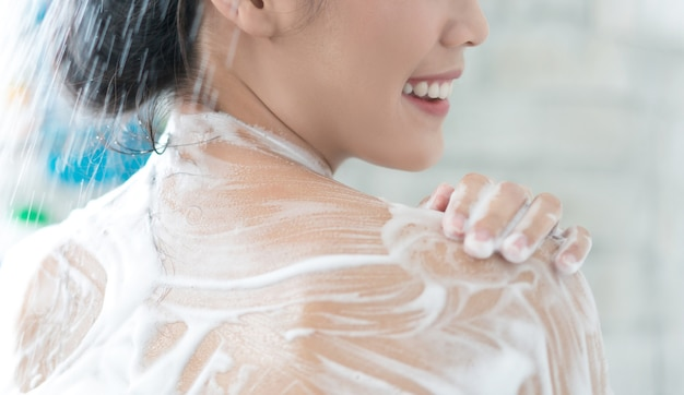 Les femmes asiatiques prennent une douche dans la salle de bain elle se frotte le savon, elle se frotte le dos Photo Premium