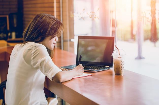 Femmes asiatiques se réveillant au café avec ordinateur portable et écrit note pensant action de projet d'entreprise Photo Premium
