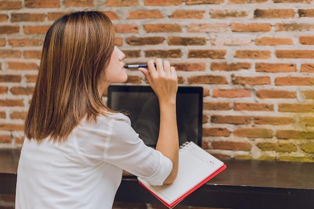 Femmes asiatiques se réveillant au café avec ordinateur portable pensant action de projet d'entreprise Photo Premium