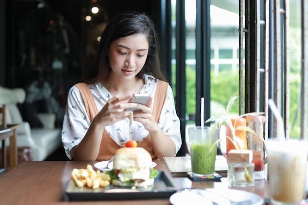 Les femmes asiatiques souriantes et heureuses ont apprécié manger des hamburgers au café et au restaurant Photo Premium
