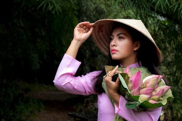 Femmes asiatiques traditionnelles avec panier de fleurs de lotus. Photo Premium