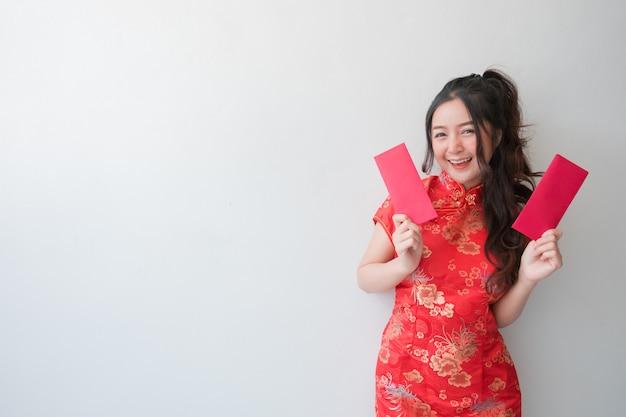 Femmes asiatiques vêtues de robes cheongsam chinois traditionnels et montrant des enveloppes rouges pour le nouvel an chinois. Photo Premium