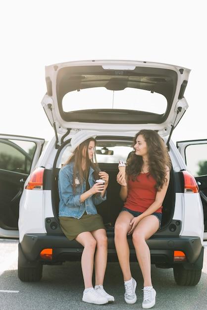 Femmes assises sur un coffre de voiture avec de la nourriture Photo gratuit