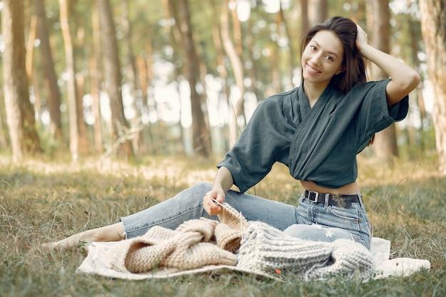 Femmes Assises Dans Un Parc D'été Et Tricot Photo gratuit