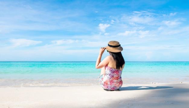 Les femmes assises sur la plage et la mer ont des vacances d'été relaxantes Photo Premium
