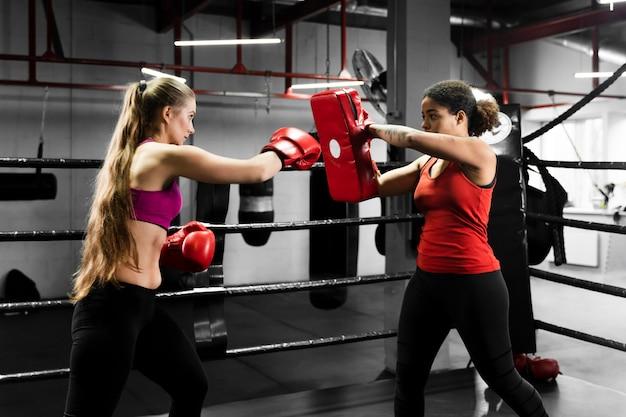Femmes Athlétiques S'entraînant Ensemble Dans Un Centre De Boxe Photo gratuit