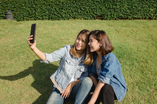 Femmes attirantes belles amis asiatiques à l'aide d'un smartphone Photo gratuit