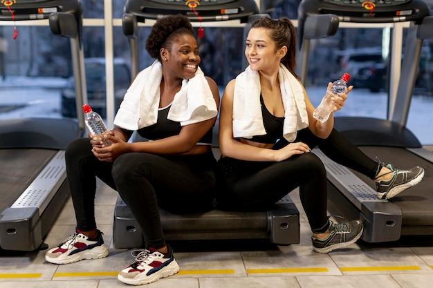 Femmes Au Grand Angle Au Gymnase En Pause Photo gratuit