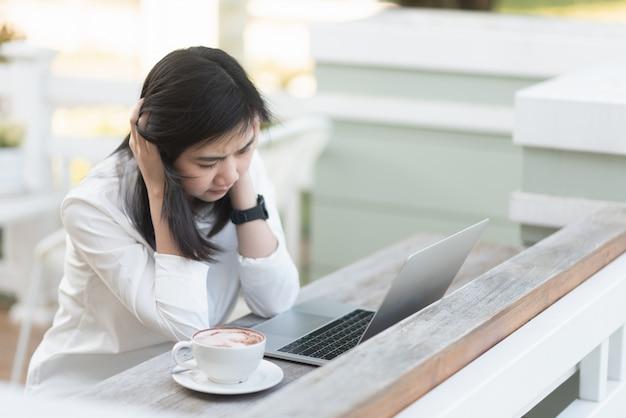 Femmes au travail qui réfléchissent fort et qui travaillent avec un ordinateur portable au café Photo Premium