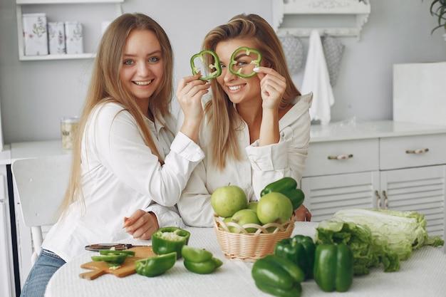 Femmes belles et sportives dans une cuisine avec des légumes Photo gratuit