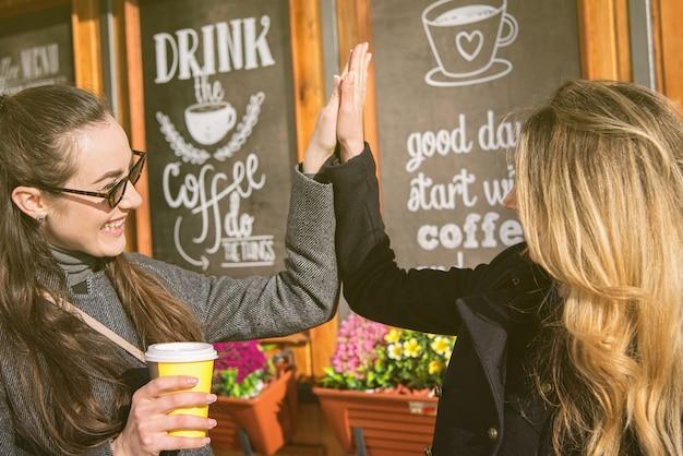 Femmes blondes et brunes buvant du café et se serrant la main Photo Premium