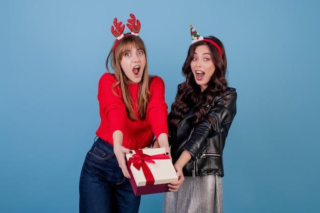 Femmes Avec Une Boîte Cadeau Avec Ruban Portant Des Cerceaux De Noël Drôles Isolés Sur Bleu Photo Premium
