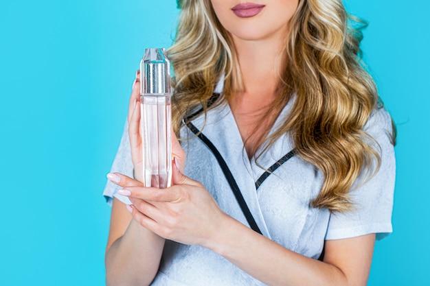 Les Femmes Avec Une Bouteille De Parfum. Belle Fille à L'aide De Parfum. Femme Avec Une Bouteille De Parfum. Femme Présente Des Parfums Parfumés. Photo Premium