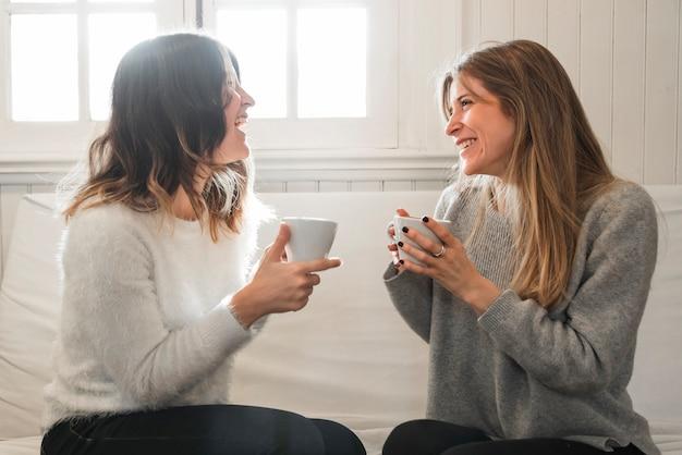 Femmes buvant du café et discutant sur un canapé Photo gratuit