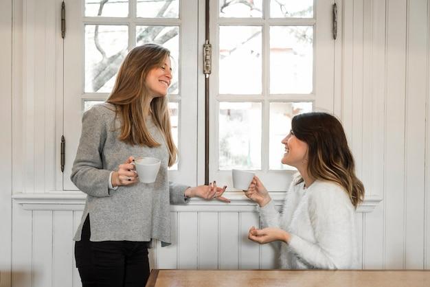 Femmes buvant du café et parlant près de la fenêtre Photo gratuit