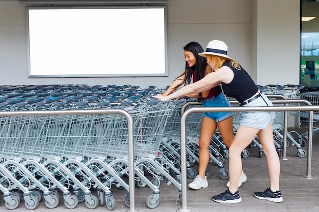 Femmes choisissant un caddie dans un parking pour chariots Photo gratuit