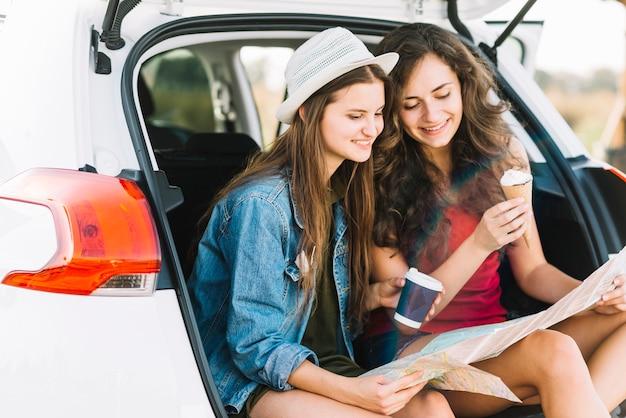 Femmes sur le coffre de la voiture avec carte Photo gratuit