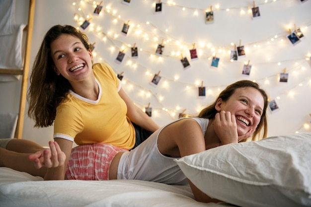 Femmes couchées sur le lit ensemble Photo gratuit