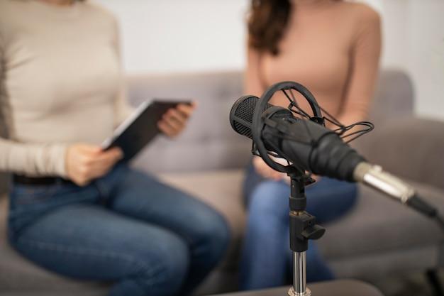 Femmes Défocalisés Faisant Une Interview Radio Avec Microphone Photo gratuit