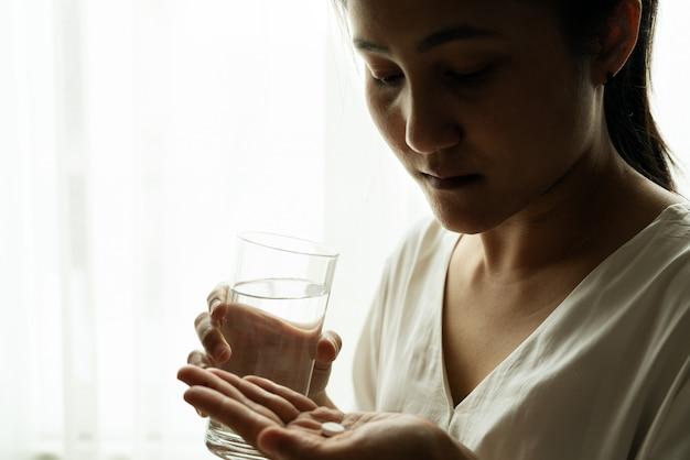 Des femmes déprimées tiennent un médicament avec un verre d'eau Photo Premium