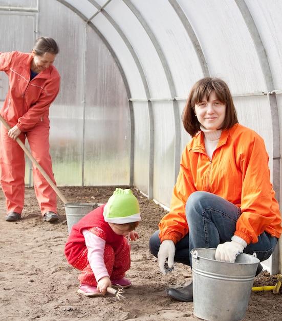 Les femmes avec des enfants travaille à la serre Photo gratuit