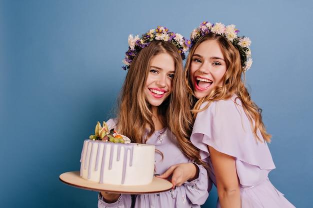 Femmes Excitées Posant Avec Un Gâteau Et Riant Sur Le Mur Bleu Photo gratuit