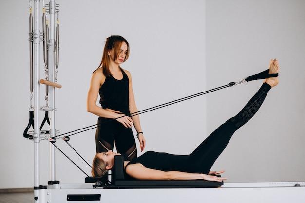 Femmes faisant du pilates sur un réformateur Photo gratuit