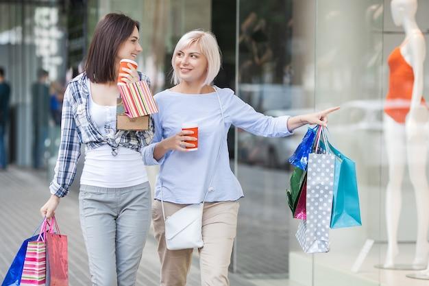 Les Femmes Faisant Du Shopping. Mère Et Fille Marchant Ensemble Sur Une Grande Vente Photo Premium