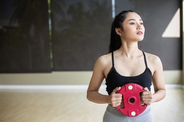 Les femmes font de l'exercice avec des disques d'haltères dans la poitrine. Photo gratuit