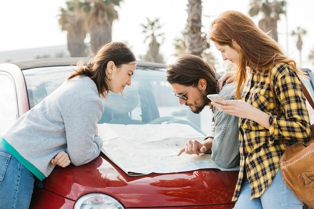 Femmes gaies avec smartphone près de l'homme regardant la carte sur le capot de la voiture Photo gratuit