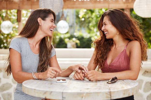 Des Femmes Heureuses Aux Cheveux Noirs Luxueux, Se Rencontrent Dans Un Café Confortable, Profitent D'une Atmosphère Calme Et D'une Intimité Photo gratuit